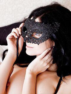 Длинноволосая брюнетка разделась в спальне и примеряет маску - секс порно фото