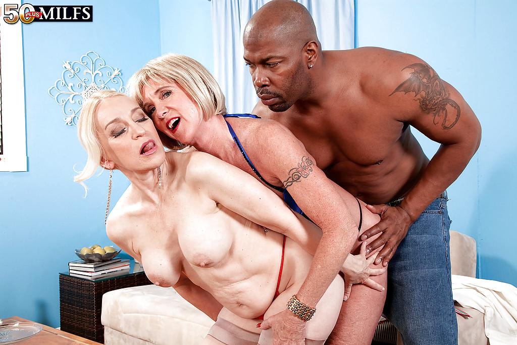 Негр трахает двух зрелых блондинок на диване - секс порно фото